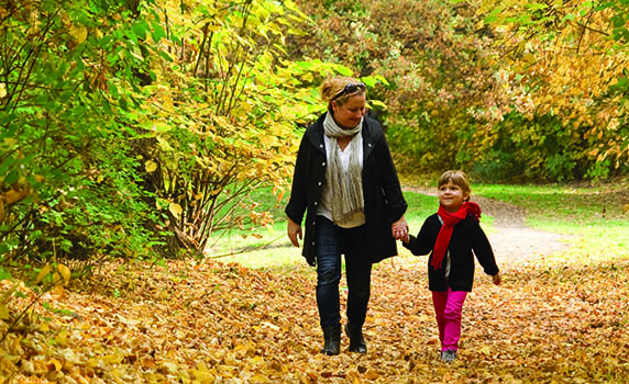 mother and daughter walking through forest in autumn