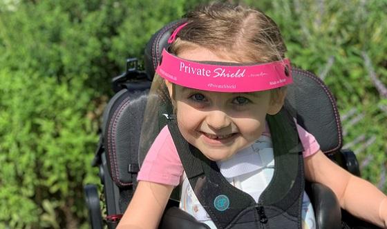 Sophia in her wheelchair wearing a face shield