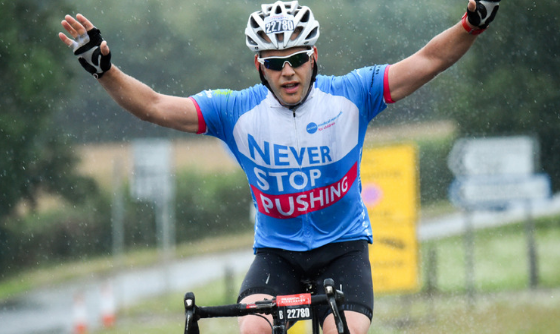 Man cycling with arms aloft