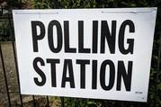 Polling station sign on metal barrier.
