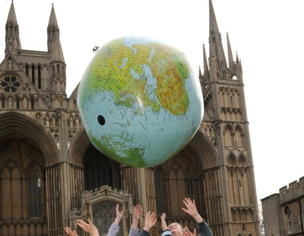 Earth ball being thrown in the air in front of Cathedral by schoolchildren.