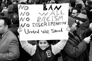 a young protester holds a sign reading no ban; no wall; no racism; no discrimination; united we stand
