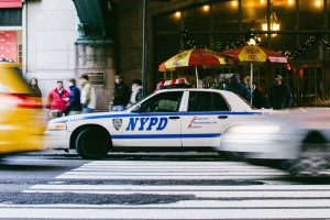 NYPD police car seen from the left side as blurred cars whiz by