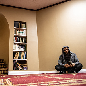 photo of our client naveed shinwari reading a book while sitting on a carpeted floor