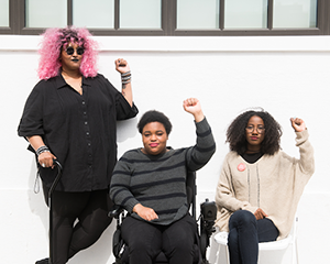 torso level photo of three Black and disabled folx (a non-binary person holding a cane, a woman in a power wheelchair, and a woman on a folding chair) raising their fists on the sidewalk in front of a white wall