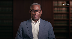 image of center for constitutional rights executive director vince warren in a still video being interviewed for VICE documentary titled photo op