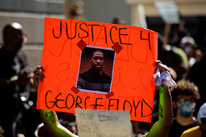 a protestor holds a sign over their head reading justice 4 george floyd