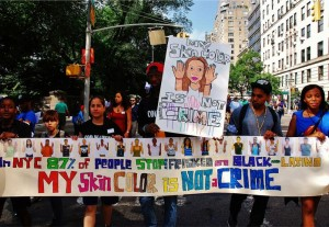 protesters march toward the camera with a banner reading my skin color is not a crime