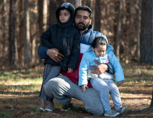 Named plaintiff Mohammad Tanvir is in a park on one knee embracing his two children who are on either side of him