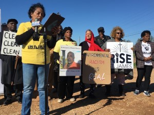 protesters stand behind a mic holding signs that say environmental racism is real