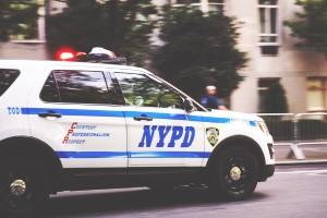 an image of an NYPD car speeding through the frame