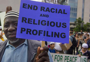 Man holds sign saying end racial and religious profiling