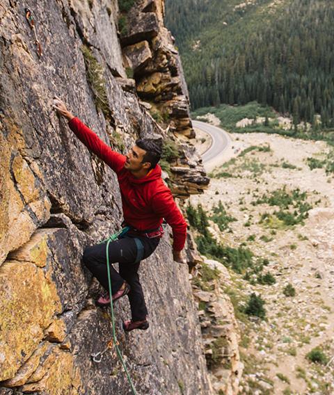 Man climbing up side of mountain