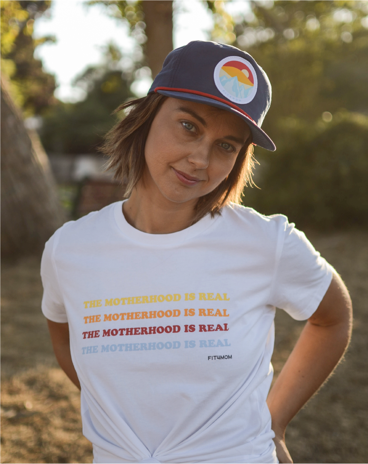 """Woman wearing a hat and shirt that reads, """"the motherhood is real"""" - shop now at shop.fit4mom.com"""